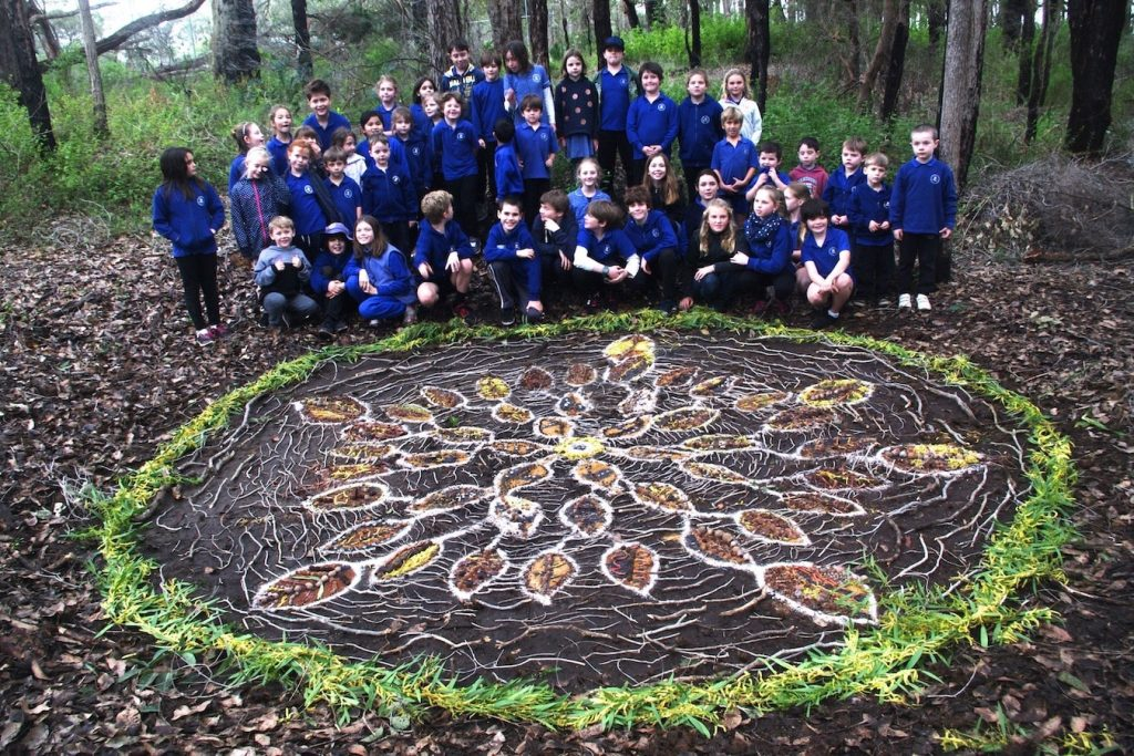 Proud primary school children showing off their land art piece 'Birds of a Feather'